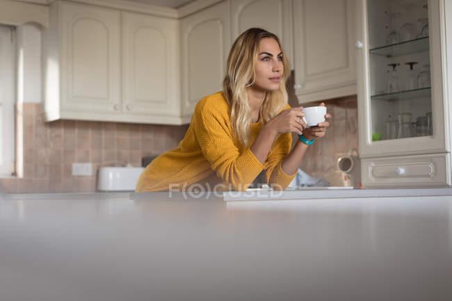 Задумчивая женщина пьет кофе на кухне дома — стоковое фото
