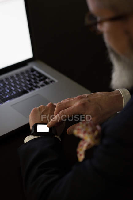 Businessman using smartwatch at desk in office — Stock Photo
