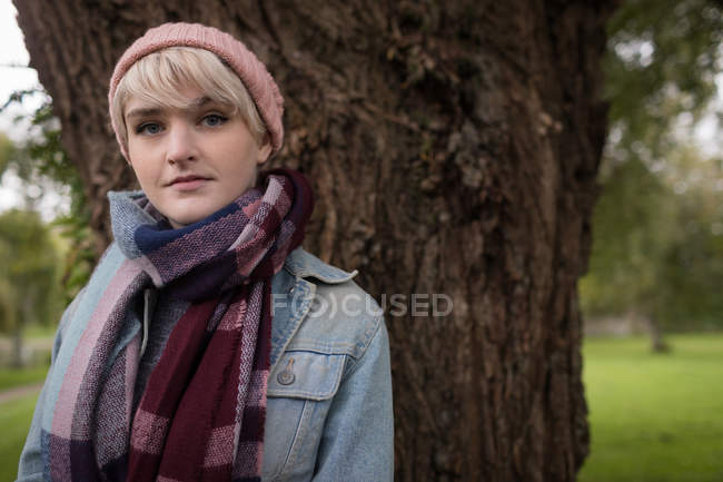 Portrait of woman in warm clothing standing in park — Stock Photo