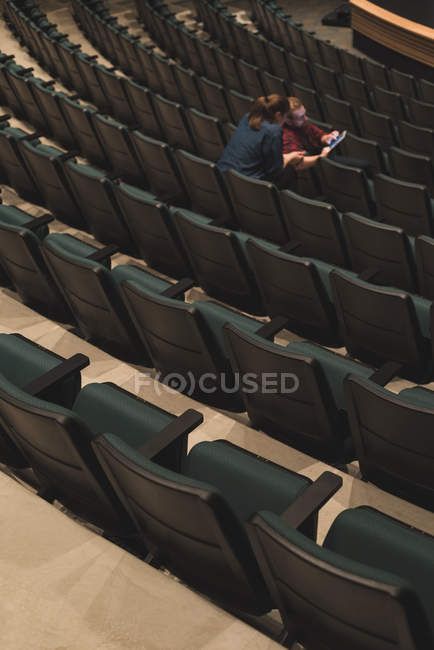 Young actors using digital tablet on seats at theatre. — Stock Photo