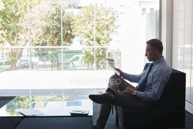 Empresário, olhando para o papel de documento no escritório — Fotografia de Stock
