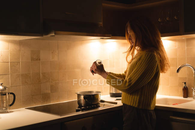 Woman preparing milk in kitchen at home — Stock Photo