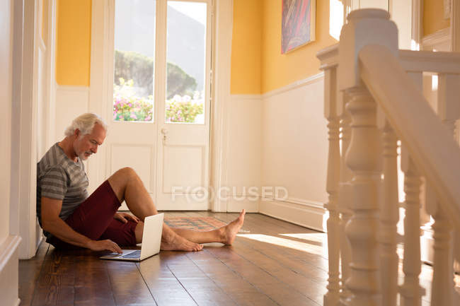 Active senior man using laptop at home — Stock Photo