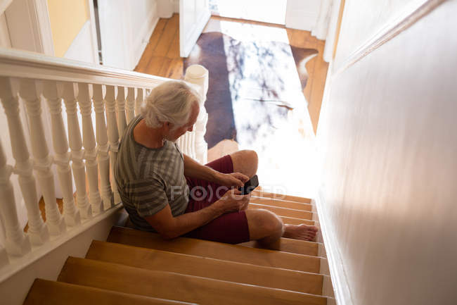Senior man using mobile phone on stairs at home — Stock Photo