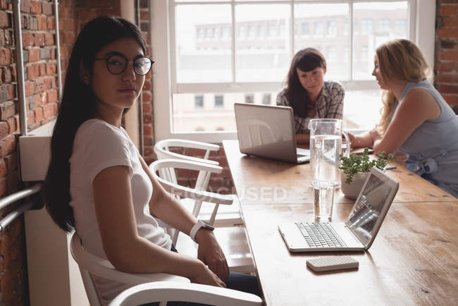 Female executive looking at camera and colleagues discussing in background at office — Stock Photo