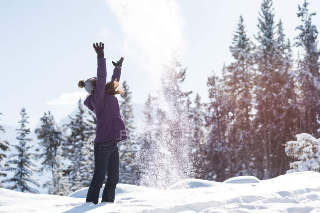 Woman throwing snow in air in wintry woodland. — Stock Photo