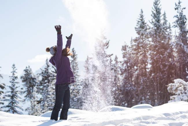 Lancio di neve in aria in un bosco invernale della donna — Foto stock
