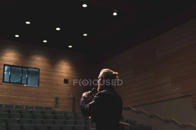 Homem praticando o discurso com o microfone no palco no teatro. — Fotografia de Stock