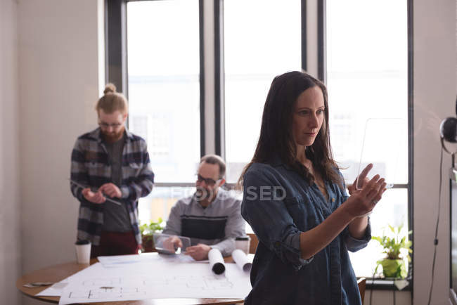 Female executive using glass digital tablet in office with colleagues working in background — Stock Photo