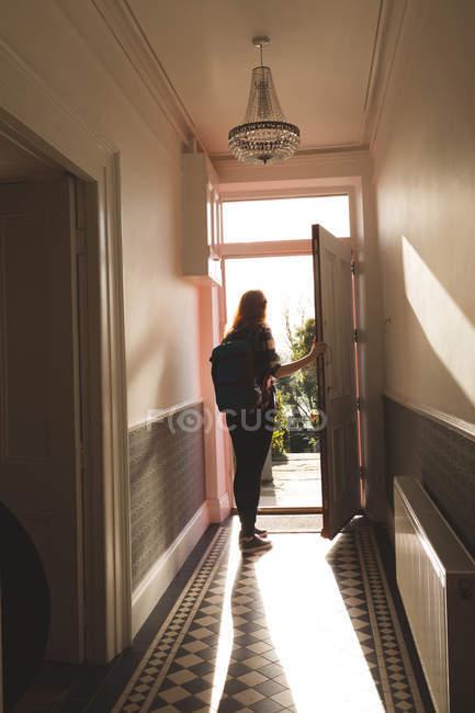 Rückansicht des Frau mit Rucksack Eröffnung Vordertür des Hauses — Stockfoto