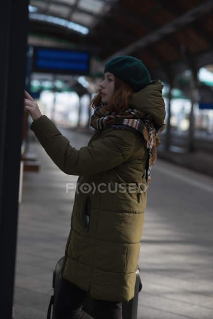 Vista lateral da mulher verificando a lista de reserva em plataforma — Fotografia de Stock