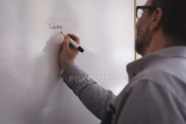 Male executive writing on whiteboard in office — Stock Photo