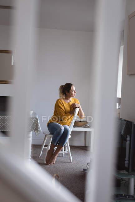 Nachdenkliche Frau sitzend auf Stuhl zu Hause — Stockfoto