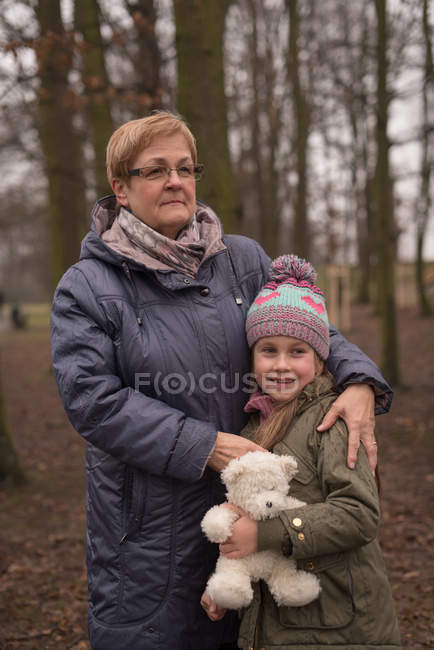 Grandmother and granddaughter standing together in forest — Stock Photo