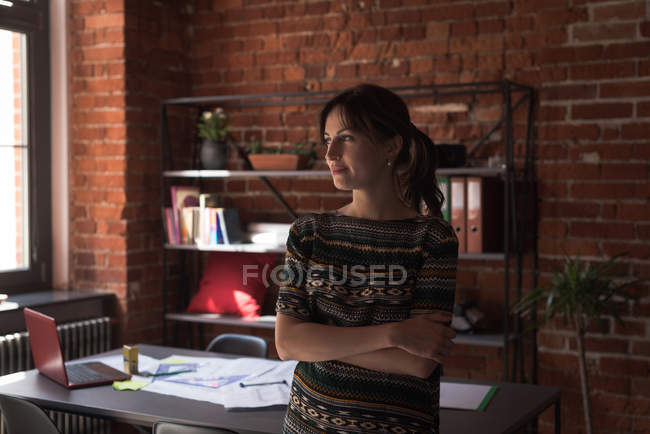 Young female executive standing arms crossed in office — Stock Photo