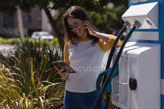 Frau benutzt digitales Tablet beim Telefonieren an Ladestation — Stockfoto