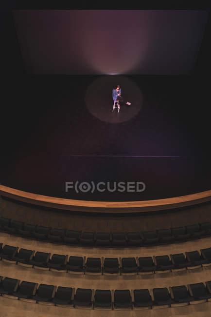 Актриса, сидя на стуле, действуя на сцену в театре. — стоковое фото