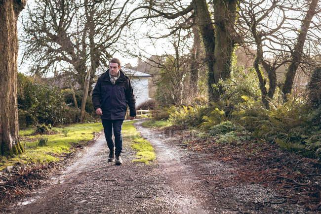 Homem andando na pista de terra em zona rural — Fotografia de Stock