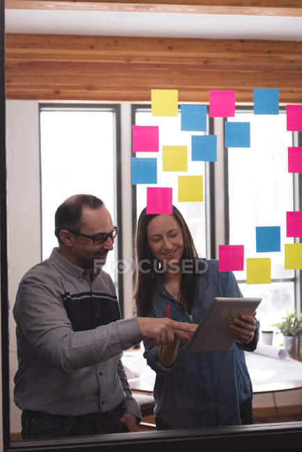 Business colleagues discussing over digital tablet in office — Stock Photo