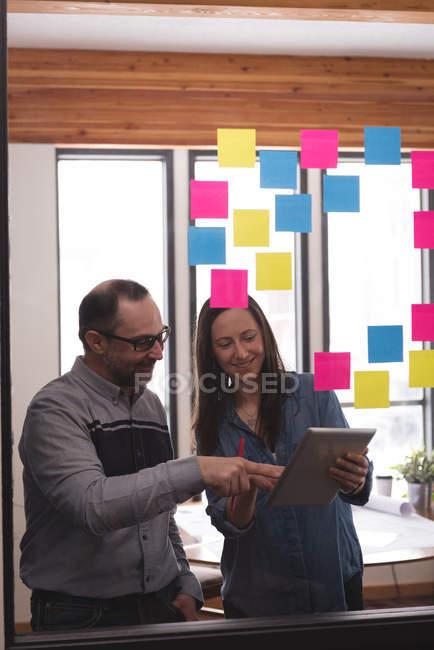Бізнес колегами, обговорювати над цифровий планшетний в офісі — стокове фото