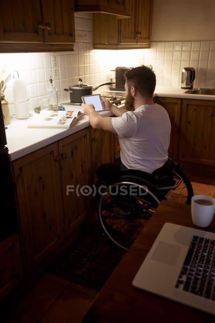 Disabled man using digital tablet in kitchen at home — Stock Photo