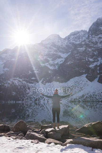 Escursionista donna in piedi con le braccia incrociate sul lungolago durante l'inverno — Foto stock