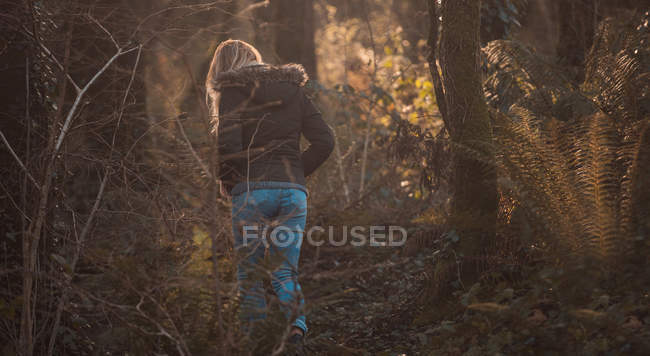Rear view of blonde woman walking  in forest. — Stock Photo