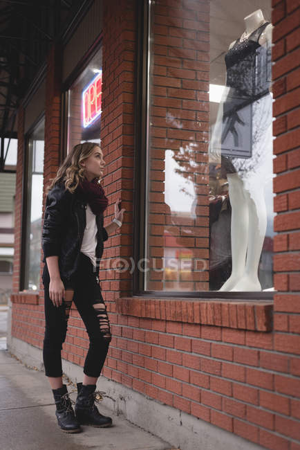 Beautiful girl looking at dress on mannequin in display — Stock Photo