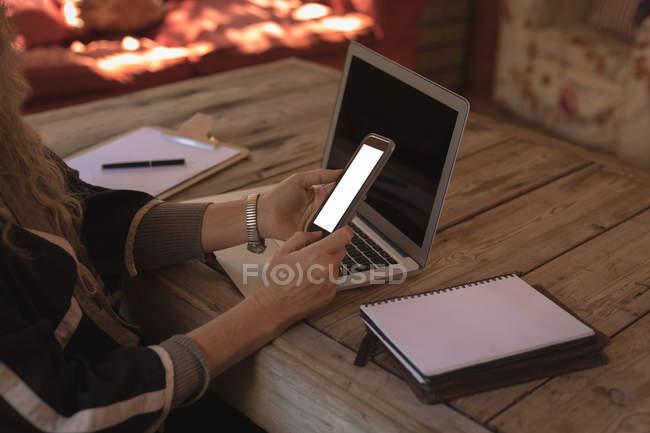 Розділ середині зрілої жінки на дому за допомогою смарт-телефон і ноутбук — стокове фото