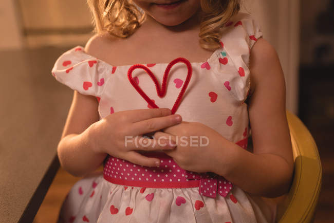 Mid section of girl holding heart shape decoration at home — Stock Photo
