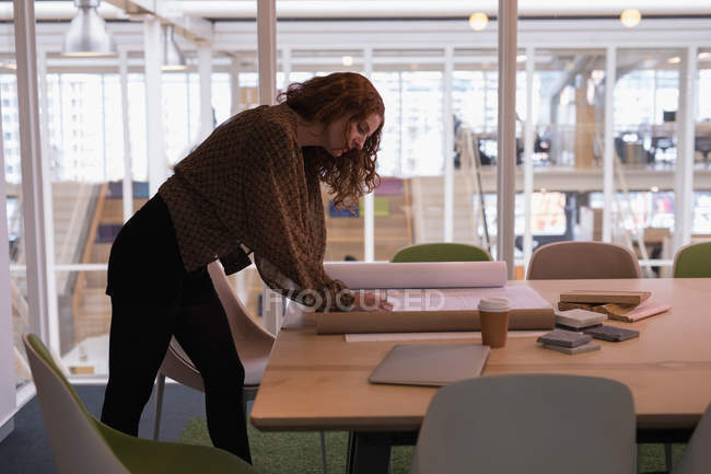 Female graphic designer working on blueprint in office — Stock Photo