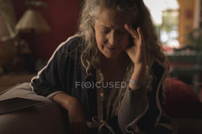 Mujer madura que sufre de dolor de cabeza en casa - foto de stock