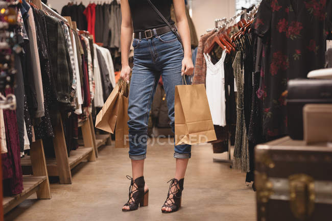 Low section of girl standing with shopping bags in mall — Stock Photo