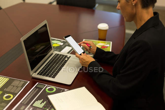 Mature businesswoman using mobile phone at desk in the office — Stock Photo