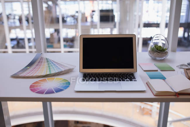 Laptop and color swatch at desk in office — Stock Photo