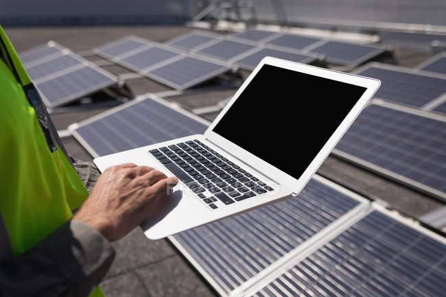 Partie médiane du travailleur masculin utilisant un ordinateur portable à la station solaire — Photo de stock