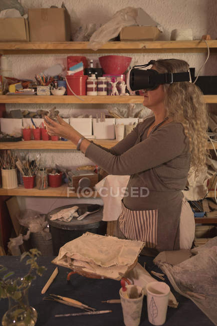 Female potter using virtual reality headset at home — Stock Photo