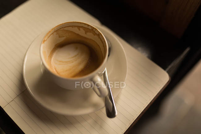 Empty cup of coffee with saucer and spoon in cafe on diary — Stock Photo