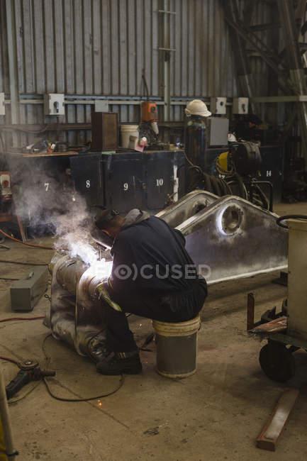 Задній вид зварювальник ремонту металокаркасу в майстерні — стокове фото