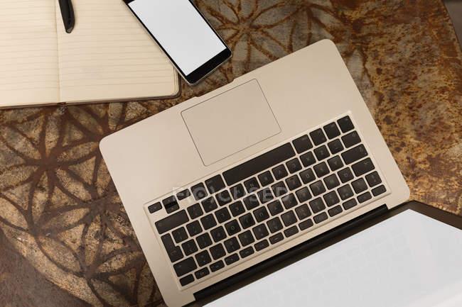 Vue du dessus de l'ordinateur portable avec téléphone portable et journal sur la table dans le café — Photo de stock
