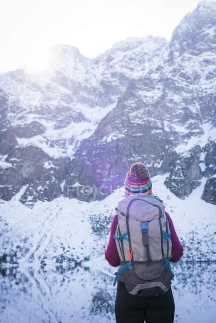 Feminino de pé com mochila à beira do lago durante o inverno — Fotografia de Stock