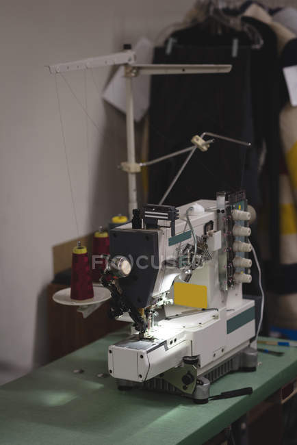 Sewing machine on table in tailor shop — Stock Photo