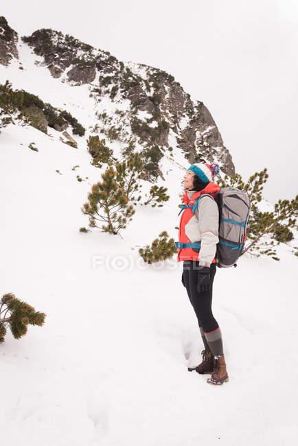 Frau steht im Winter mit Rucksack — Stockfoto