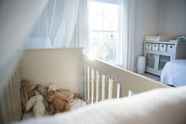 Primer plano de la cuna de madera con juguetes blandos en casa - foto de stock
