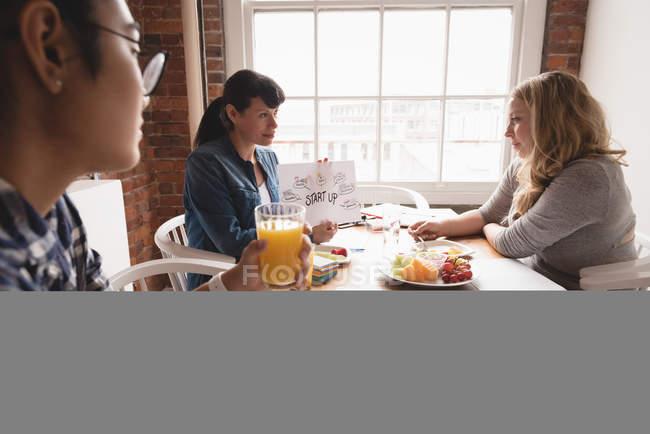 Femmes cadres discutant entre eux tout en prenant son petit déjeuner dans la salle de réunion — Photo de stock