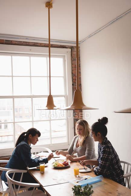 Femmes cadres prenant son petit déjeuner ensemble au bureau créatif — Photo de stock