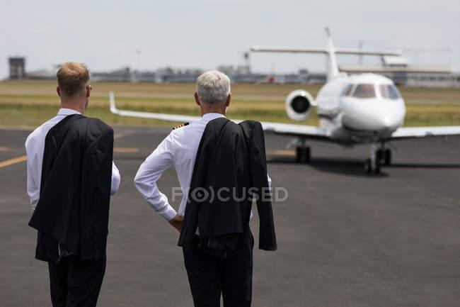 Вид сзади двух мужчин пилотов, стоя на взлетно-посадочной полосы — стоковое фото