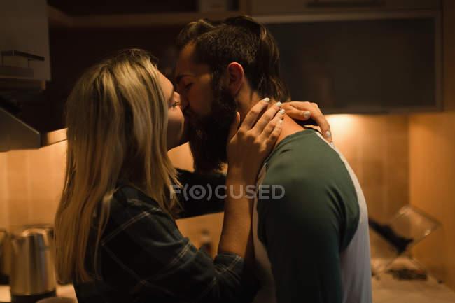 Paar küsst sich in Küche zu Hause — Stockfoto