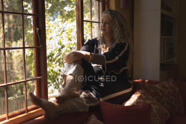 Nachdenklich Reife Frau sitzt auf der Fensterbank zu Hause — Stockfoto