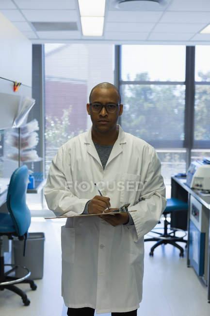 Portrait de scientifique masculin avec presse-papiers debout dans le laboratoire — Photo de stock